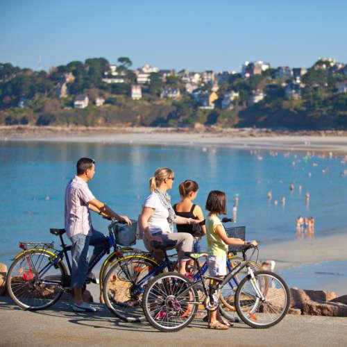 Famille et ses vélos devant une plage Tour de Manche