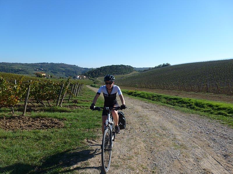 Femme à vélo sur chemin de terre entre vignes Abicyclette Voyages