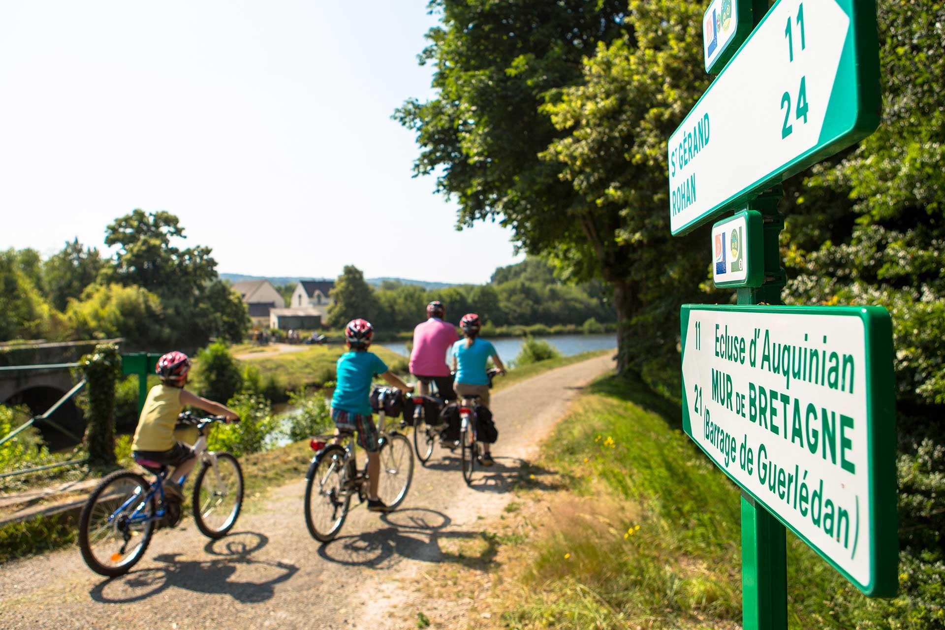 Famille à vélo passant devant des panneaux d'indication de véloroutes