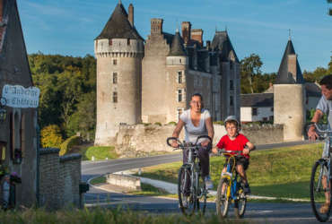 Parents et leur garçon à vélo devant le château de Montpoupon