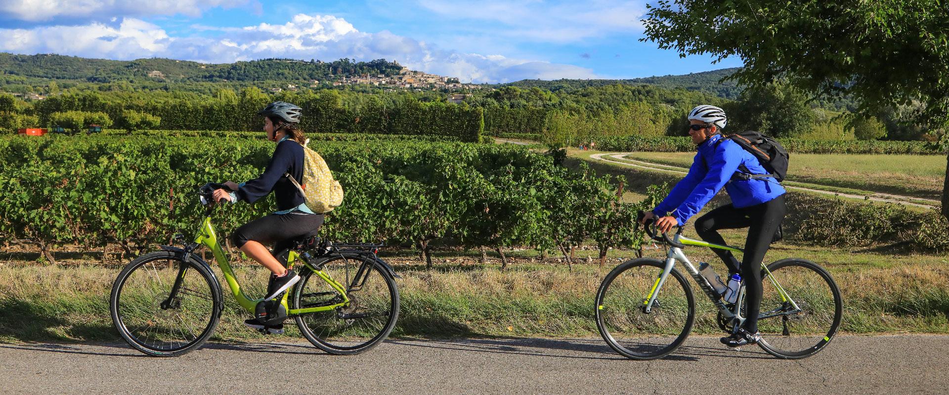 Couple à vélo route vigne village provençal