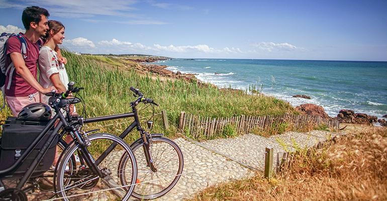 Couple avec vélo face à la mer sur la cote Atlantique