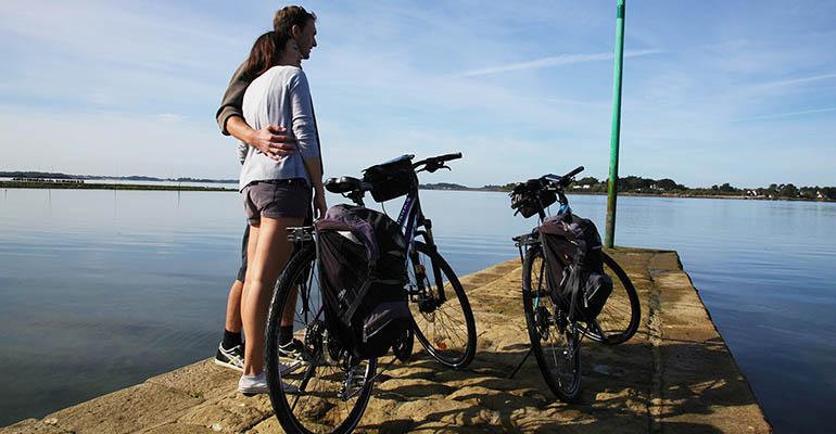 Cyclistes avec leurs vélos contemplant le Golfe du Morbihan