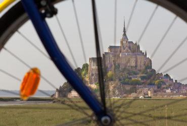 Le Mont Saint-Michel vu à travers les rayons d'un vélo Abicyclette Voyages à vélo