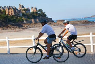 2 cyclistes sur une promenade devant la la plage