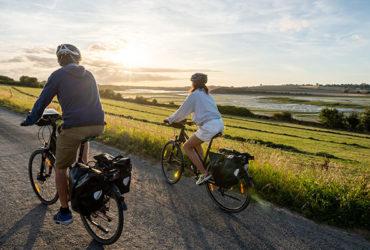 couple à vélo au soleil couchant sur les bords de la Rance