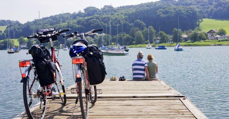 2 voyageurs et leurs vélos sur un ponton au bord d'un lac avec voiliers Salzbourg et le pays des lacs à vélo Abicyclette Voyages
