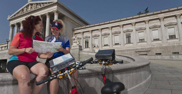 2 femmes et leurs vélos devant monument avec drapeau de l'Autriche Le Danube de Passau à Vienne