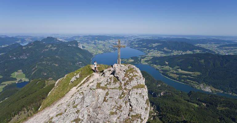 Croix au sommet d'un piton rocheux surplombant paysage du pays des lacs dans la région de Salzbourg Abicyclette Voyages