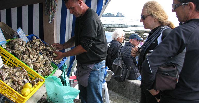 Touristes à vélo devant l'étal d'un marchand d'huîtres Abicyclette Voyages à vélo