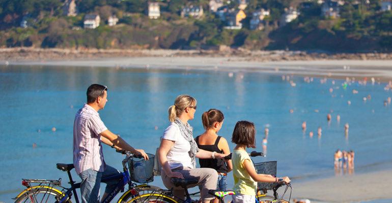 Famille à vélo devant la plage La Côte d'Émeraude et ses terres à vélo Abicyclette Voyages