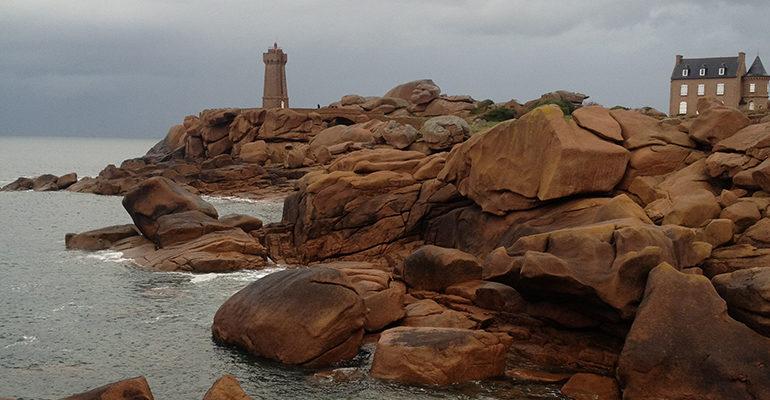 Phare et maison en pierre sur la côte de granit rose Le Tour de Manche à vélo Abicyclette Voyages