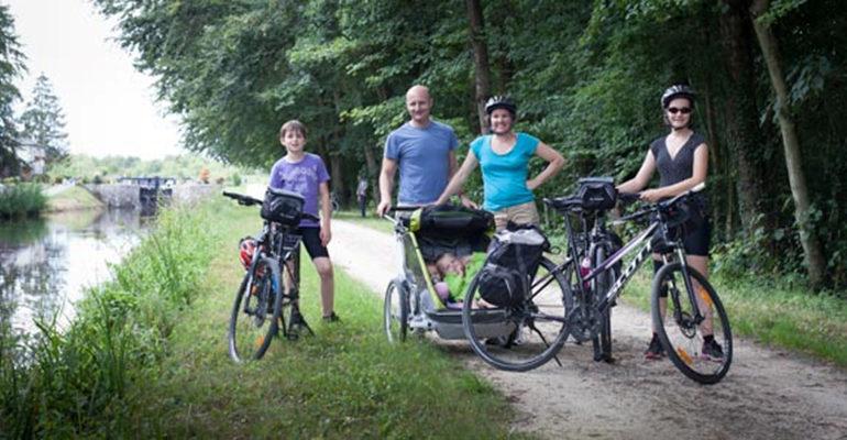 Famille à vélo pose devant le canal Le Canal d'Ille et Rance à vélo