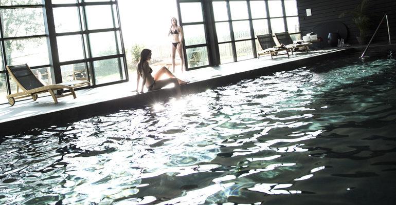 2 femmes au bord de la piscine couverte Eco-hôtel Spa 4 étoiles La Grée des Landes à La Gacilly Abicyclette Voyages à vélo
