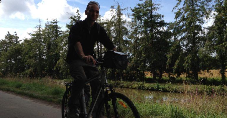 Homme à vélo devant une rangée de samins La Vélodyssée : De Roscoff à Nantes