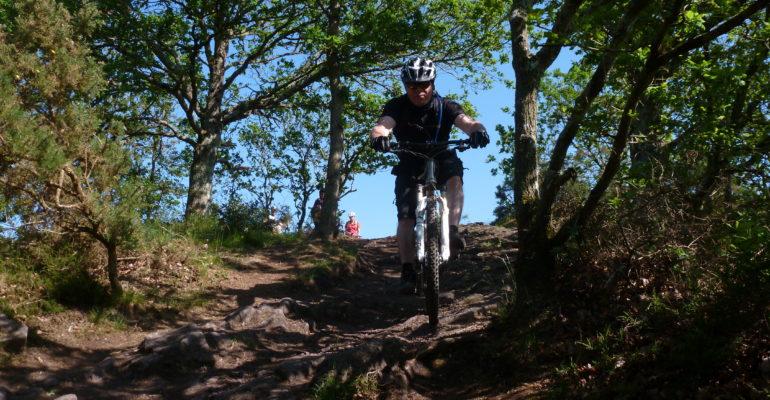 Homme à VTT dans une descente VTT en Suisse Normande Abicyclette Voyages à vélo