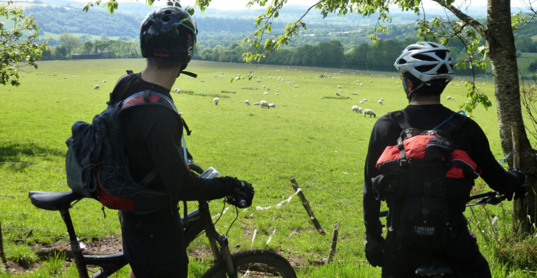2 hommes en VTT observant la campagne VTT en Suisse Normande Abicyclette Voyages à vélo