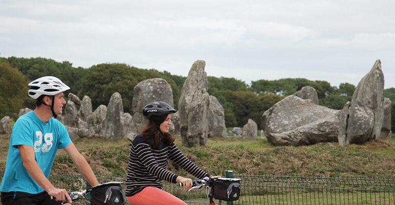 Couple à vélo devant l'alignement de menhirs de Carnac Le Tour du Golfe du Morbihan