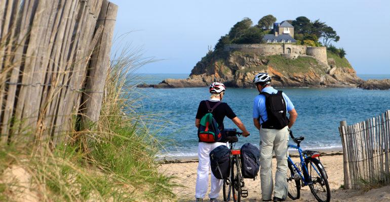 Couple de cycliste sur la plage face à l'ile de Duguesclin De Saint-Malo aux plages du débarquement Abicyclette Voyages à vélo