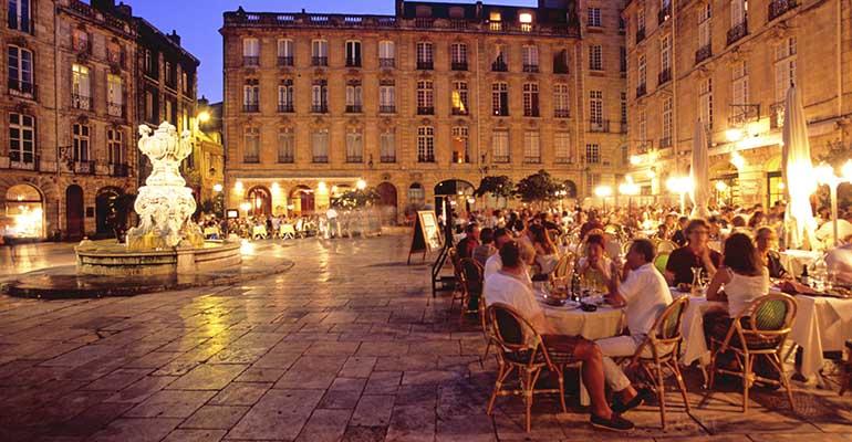 Place de Bordeaux à la tombée de la nuit avec fontaine et terrasses de restaurant