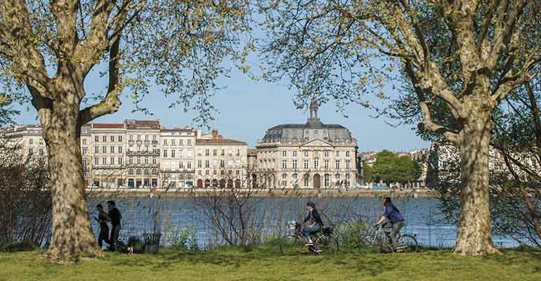 Cyclistes longeant la Garonne en face de la vieille ville de Bordeaux