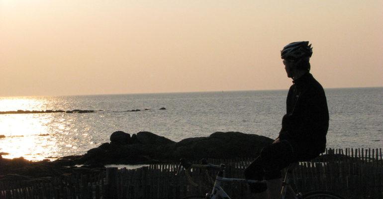 Cycliste devant coucher de soleil sur le bord de mer Grande Traversée à vélo de la Bretagne nord Abicyclette Voyages