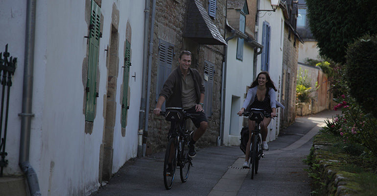 Couple à vélo dans une ruelle Golfe du Morbihan Abicyclette Voyages à vélo