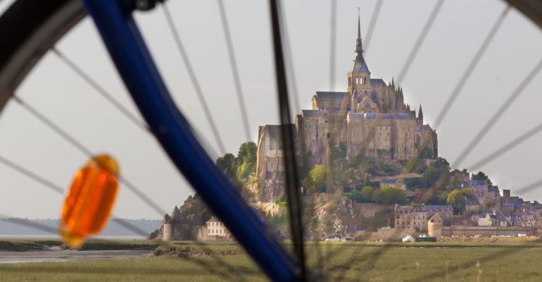 Vue du Mont Saint Michel à travers les rayons d'un vélo Abicyclette Voyages à vélo