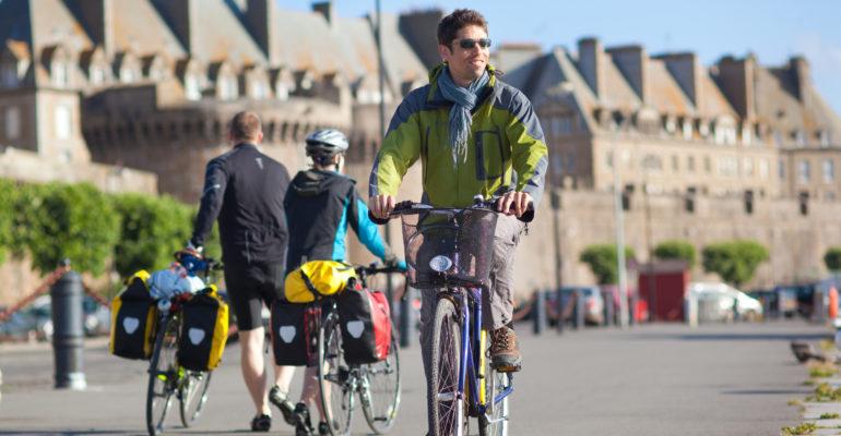 Homme à vélo devant les remparts de Saint Malo La Baie du Mont Saint-Michel à vélo Abicyclette Voyages
