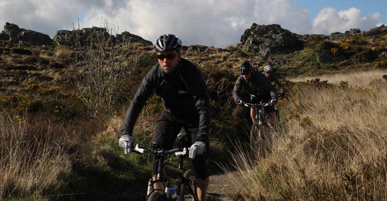 3 hommes à VTT dans une descente VTT A l'assaut des Monts d'Arrée Abicyclette Voyages à vélo