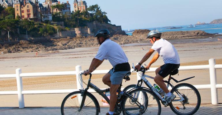 Cyclistes sur un ponton le long de la mer à Dinan La Côte d'Émeraude et ses terres à vélo Abicyclette Voyages