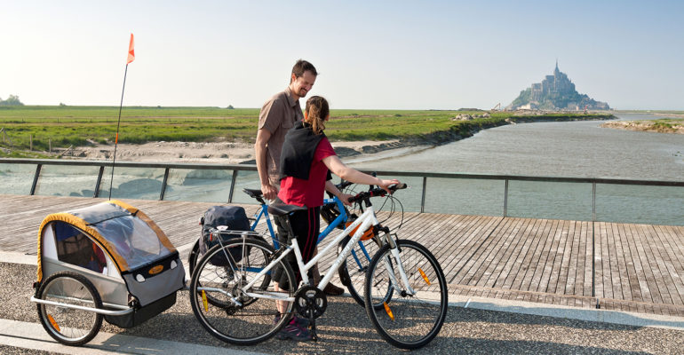 Cyclistes avec remorque observent le Mont Saint Michel La Baie du Mont Saint-Michel à vélo