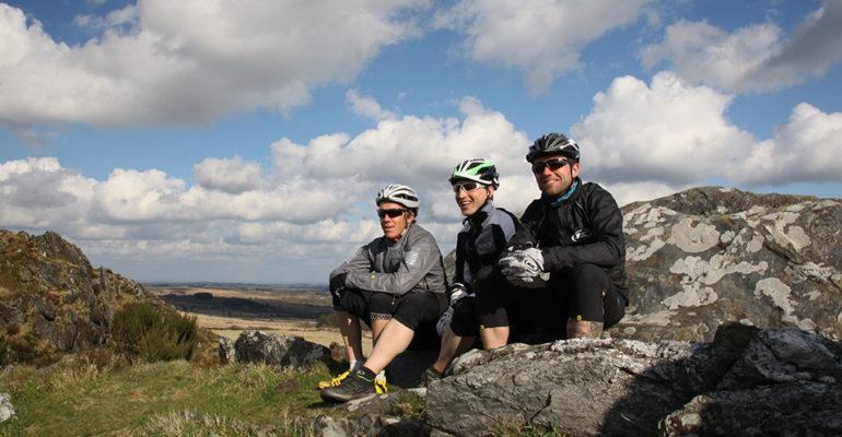 3 cyclistes assis sur un rocher VTT A l'assaut des Monts d'Arrée Abicyclette Voyages à vélo