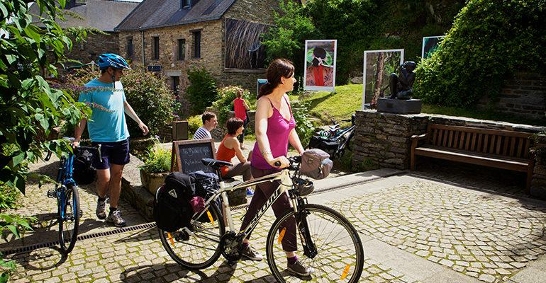 Couple vélos à la main visitant le village de la Gacilly Abicyclette Voyages à vélo
