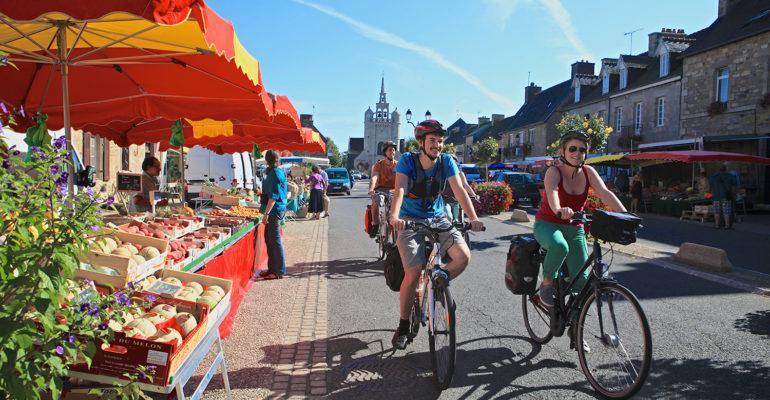 Cyclistes devant un étal de marché Le Tour de Manche à vélo Abicyclette Voyages