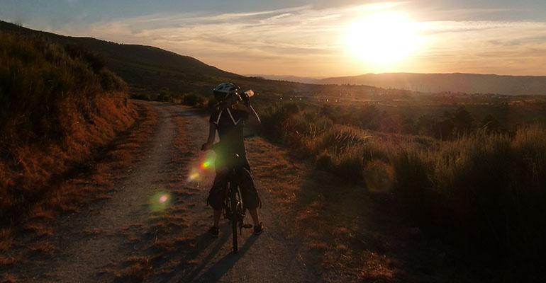 Cycliste buvant devant paysage de soleil couchant La vallée du Douro