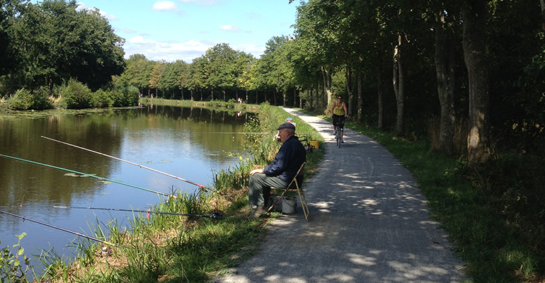 Pecheur et cycliste le long du canal Le Canal d'Ille et Rance à vélo