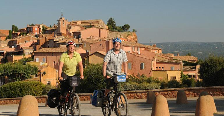 Couple à vélo en danseuse à la sortie d'un village Le petit tour du Luberon Abicyclette Voyages à vélo