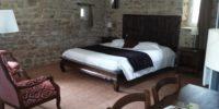 Chambre avec mur en pierres Hôtel logis la bastide à saint bach Abicyclette Voyages à vélo
