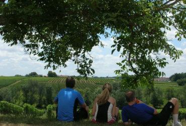 3 cyclistes assis contemplant les vignes du Parigord Abicyclette Voyages à vélo
