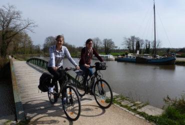 2 femmes à vélo traversant un pont enjambant le Canal d'Ille et Rance