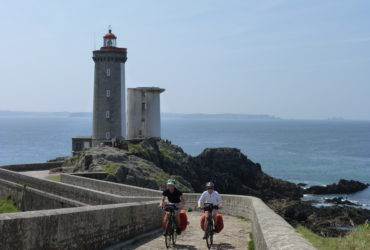 Couple de cyclistes quittant un phare en Bretagne