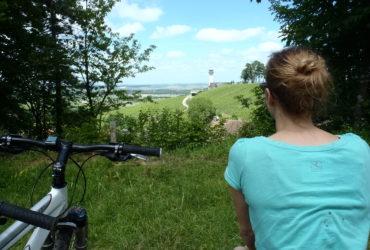 Femme observant un paysage de vignobles La Méthode Champenoise Abicyclette Voyages à vélo