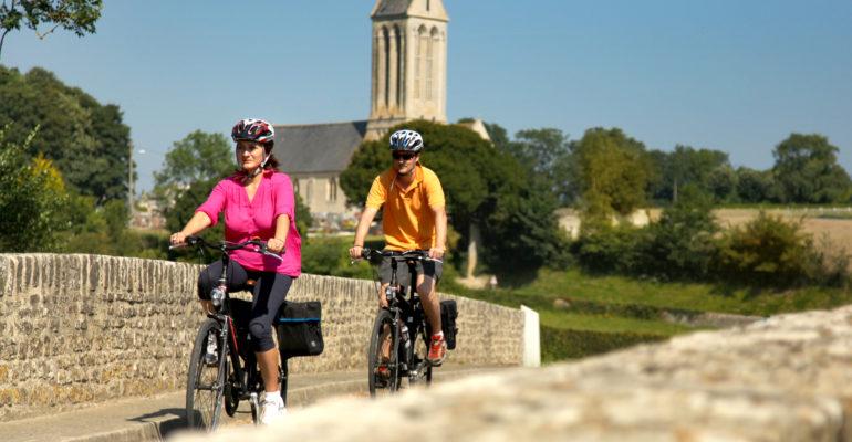 Couple de cycliste traversant un pont Vélo-Etreham Abicyclette Voyages à vélo