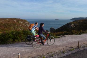 Couple de cyclistes longeant la côte et le Cap Frehel