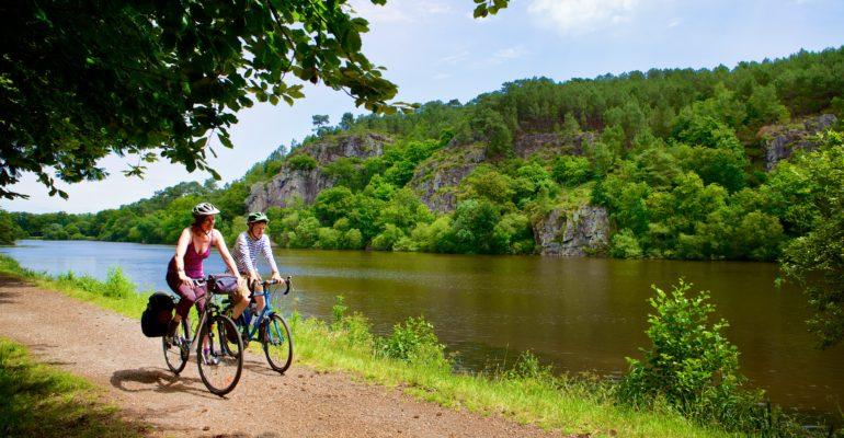 Couple de cyclistes sur le site de l'Ile aux pies sur la riviere de l'Oust Abicyclette Voyages à vélo