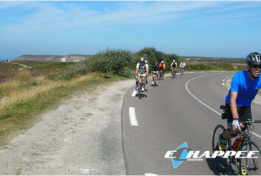 Cyclistes sur route devant le Cap Frehel Grande Traversée de la Bretagne nord