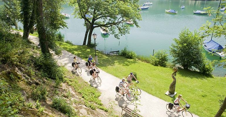 Groupe de cycliste sur piste le long d'un lac Salzbourg et le pays des lacs Abicyclette Voyages à vélo