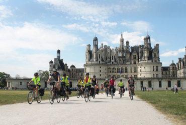 groupe de cyclistes en selle devant le château de chambord