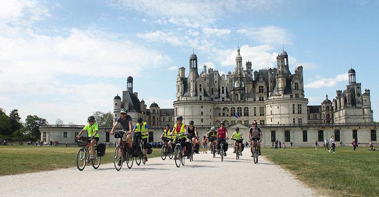 groupe de cyclistes en selle devant le château de chambord Abicyclette Voyages à vélo
